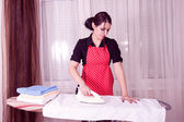 Young beautiful woman ironing clothes — Stock Photo