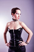 Sexy woman with hourglass figure in black leather corset — Stock Photo