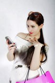 Young woman holding the cell phone and shopping bag — Stock Photo