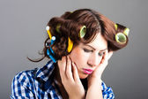 Portrait of sexy housewife with curlers and headache — Stock Photo