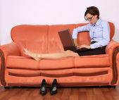 Empresaria en el sofá y trabajando en el ordenador portátil — Foto de Stock