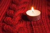 Candles on red knitted background — Stockfoto
