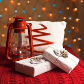 Christmas lantern with presents, ornaments and pillow — Stock Photo