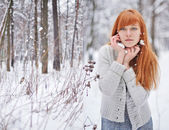 Beautiful red-haired girl in a snowy forest — Stock Photo