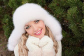 Girl with toothy smile in winter fir forest — Stock fotografie