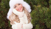 Girl with toothy smile in winter fir forest — Stok fotoğraf
