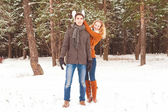 Young couple have a walk in the winter park — Stock Photo