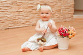 Little girl in white dress with a smart flower on her head smiling and rejoicing — Stock Photo