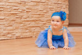 Little girl in blue ballet skirt with a flower on her head smiling and rejoicing — Stock Photo