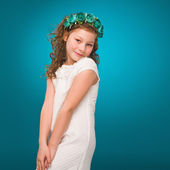 Kid. Air kiss. Girl smiling and looking at the camera in a white dress and a wreath on a turquoise background — Stock Photo