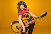 Guitarist. Child. Girl playing guitar. Small kid in a cap and T-shirt. — Stock Photo