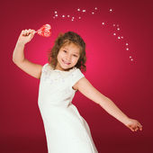 Lollipop. Heart. Candy. Little girl with lollipop in her hand on red background — Stok fotoğraf