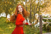 Romantic portrait of the woman in airy red dress dancing — Stock Photo