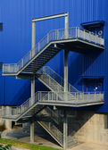 Stairs on the outside of blue building — 图库照片