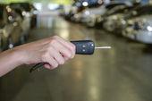 Hand with a Car keys in car park — Stock Photo