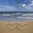 Drawing hearts in the sand — Stockfoto