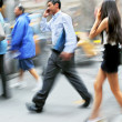 Motion blurred business people walking on the street — Photo