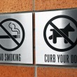 Curb your dog and no smoking signs — Stock Photo