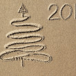 Christmas tree and 2014 year written on the beach sand — Stock Photo