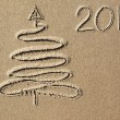 Stock Photo: Christmas tree and 2014 year written on the beach sand