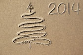 Christmas tree and 2014 year written on the beach sand — Stok fotoğraf