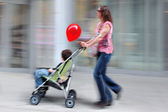 Mother with her baby in a stroller — Stock Photo