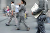 Motion blurred business people walking on the street — Stockfoto