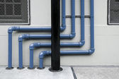 Colorful of pipes under the modern building — Stock Photo