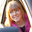 Smiling beautiful girl looks out of a car window — Stock Photo
