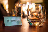 Reserved sign next to a tumbler glass — Stok fotoğraf