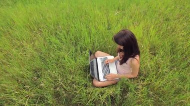 Female student working on laptop computer in the park — Stock Video