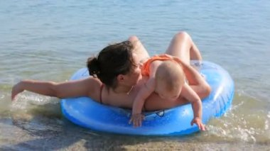 Mother with her little baby swimming in the sea with inflated ring — Stock Video