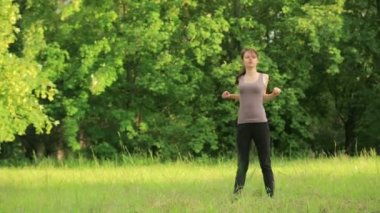 Young attractive woman doing exercise in park — Стоковое видео
