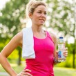 Attractive blond woman with a water bottle and towel — Стоковая фотография