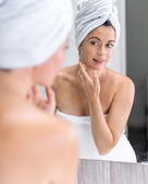 Middle aged woman looking at herself in the mirror — Stock Photo