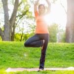 Girl meditating and doing yoga at sunset — Stock Photo