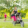 Mother running in the park — Stock Photo