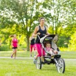 Mother running in the park — Stockfoto