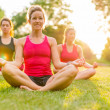 Women doing yoga outdoors at sunset — Stock Photo