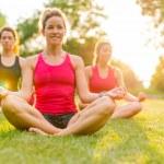 Women doing yoga outdoors at sunset — Stock Photo