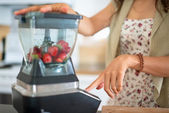 Health conscious woman using a blender — Stock Photo