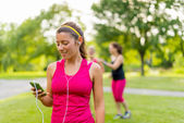 Listening to music helps her workout — Stock Photo