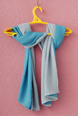 Double-sided silk scarf on yellow coat-hanger — Stock Photo