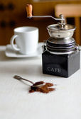 Spoon with ground coffee end coffee-grinder on the table — Stock Photo