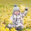 Lovely baby age of 1 year outdoors in autumn plays with leaves — Stock Photo