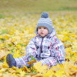 Lovely baby age of 1 year outdoors in autumn against leaves — Stock Photo
