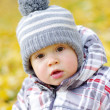Portrait of lovely baby outdoors in autumn against yellow leaves — Stock Photo