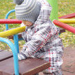 Baby plays outdoors in autumn on playground — Stock Photo