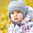 Baby boy outdoors in autumn against yellow leaves — Stock Photo