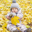 Lovely baby with yellow leaf outdoors — Stock Photo
